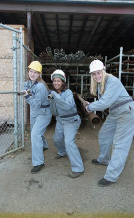 BCIT women in trades; plumbing, students in uniforms and hard hats carrying piping material [5 of...