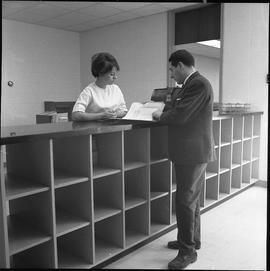 BCVS Graphic arts ; two people standing at a shelf and looking at papers [2 of 2]