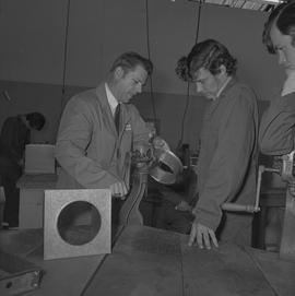 Sheet metal, 1968; instructor showing a student how to use a tool to shape sheet metal ; students...