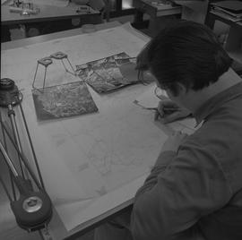 Map drafting, Victoria, 1968; man measuring a drafted map ; aerial photographs and stereoscope on...