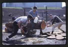 Lumberjack event; two men competing in a double buck sawing competition and a man sitting on the ...
