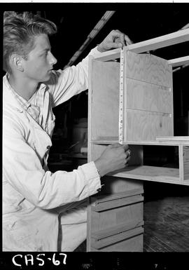 B.C. Vocational School image of a Carpentry Trades student measuring shelves in the Carpentry shop.