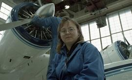 Canadian women at work; woman in uniform in front of an airplane inside a hangar [3 of 3 photogra...