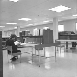 BCIT Library ; man sitting at a desk reading a book