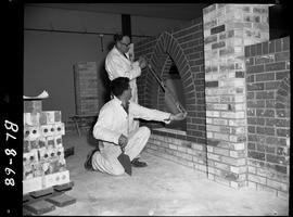 B.C. Vocational School image of a Bricklaying student with an instructor checking a brick arch op...
