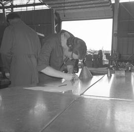 Sheet metal, 1968; student cutting a piece of sheet metal ; people working in background