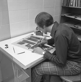 BCVS Graphic arts ; man reading a poster and holding a pen