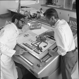 BCVS Graphic arts ; two men discussing a advertisement poster