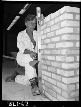 B.C. Vocational School image of a Bricklaying student checking that a brick structure is level