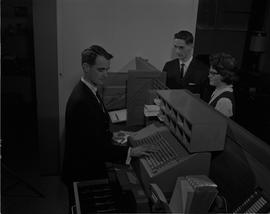 Hotel Motel, 1966; man in a suit using a cash register at a staged hotel reception desk, two peop...