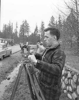 Survey, 1964; a man using a surveying level and another man holding a measuring tape [2 of 2]