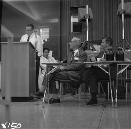CVA Convention, 1969 ; man standing at a podium ; two men sitting at a table watching
