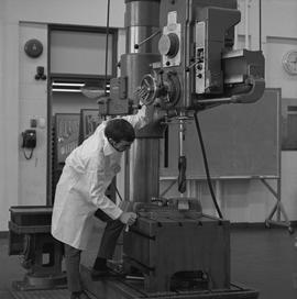 Mechanical technology, 1968; man in a lab coat using a large drill [2 of 2]