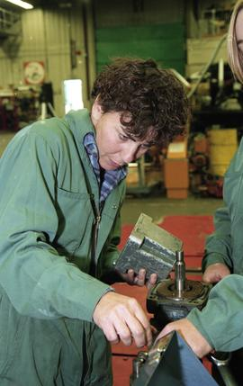 BCIT women in trades; heavy duty, students in uniforms using mechanical tools and equipment [8 of...
