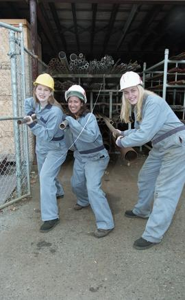 BCIT women in trades; plumbing, students in uniforms and hard hats carrying piping material [6 of...