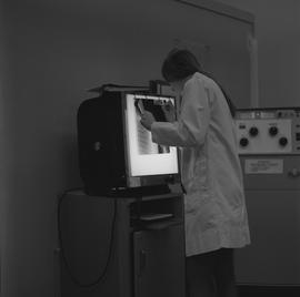 Medical radiography, 1968; woman in a lab coat writing on an x-ray hanging up on a light board