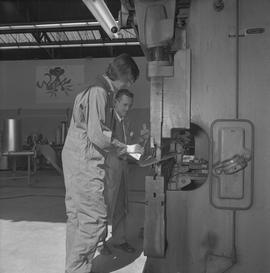 Sheet metal, 1968; instructor and student using machinery to shape a piece of sheet metal ; works...