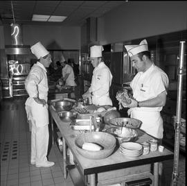BC Vocational School Cook Training Course ; instructor talking to a student preparing food ; othe...