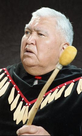 Bob George, First Nations elder, in First Nations garment playing an instrument [34 of 36 photogr...