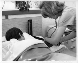 BCVS Nursing student with stethoscope and patient in bed [1 of 2 photographs]