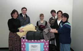 "Staff members with a box labeled ""Warm clothes and blankets for the needy"" [4 of 5 phot..."