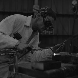 Welding, 1968; man wearing protective goggles welding [2 of 6]