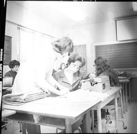 BC Vocational School Commercial Program; instructor and student looking at a book ; students in b...