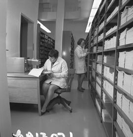 BCVS Graphic arts ; two women working ; a room with shelves of books