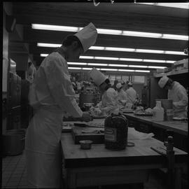 BC Vocational School Cook Training Course ; student preparing food on a chopping block ; students...